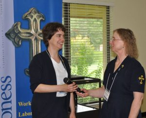 After four years as president of Concordia Deaconess Conference (CDC), Cheryl D. Naumann, right, of Oakmont, Pa., hands the microphone over to newly elected President Jennifer M. Phillips of Monroeville, Ind., during the CDC's annual conference June 23-25 in Winter Park, Fla. (Sara Smith)