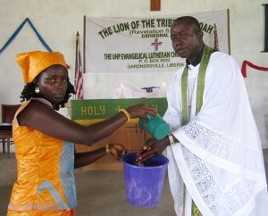 The Rev. Amos Bolay, president and bishop of the Evangelical Lutheran Church of Liberia, demonstrates the pre-Communion hand-washing technique used to help stop the spread of the Ebola virus in Liberia. (Courtesy of Amos Bolay)