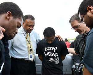 The Rev. Roosevelt Gray Jr., director of LCMS Black Ministry (second from left), and the Rev. Steven Schave, director of LCMS Urban & Inner-City Mission (second from right), pray with others along West Florissant Avenue in Ferguson, Mo., on Aug. 18. (LCMS/Erik M. Lunsford)