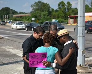 The Rev. Ross Johnson, director of LCMS Disaster Response, and the Rev. Steven Schave, director of LCMS Urban & Inner-City Mission, pray with people along West Florissant Avenue in Ferguson, Mo., on Aug. 18. (LCMS/Erik M. Lunsford)