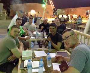 """Airmen at Al Udeid Air Base in Qatar study Luther's Small Catechism and tend to cigars during one of their """"Holy Smokes"""" Bible studies."""