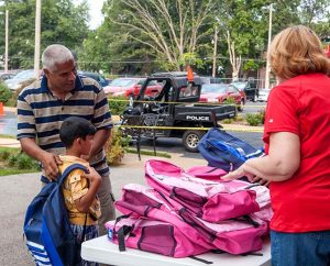 """A young student tries on his backpack filled with school supplies and a Bible-story book, courtesy of Concordia Publishing House's """"Operation F.U.N."""" (For a United Neighborhood), held Aug. 6 on the publisher's parking lot in St. Louis. (Concordia Publishing House)"""