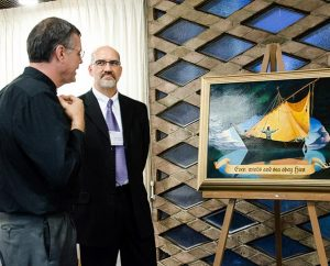"""At the LCMS International Disaster Conference, artist Edward Riojas, right, shows his painting titled """"Even Winds and Sea Obey Him"""" to LCMS Eastern District Response Coordinator Rev. Kristian Bjornstadt.  Riojas presented the painting to the pastor of St. John Lutheran Church, Pilger, Neb., whose building was torn apart by twin tornadoes earlier this year.  International representatives at the conference received a print of the artwork. (LCMS/Pamela J. Nielsen)"""