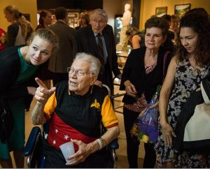 "The Rev. Otto J. Hintze, commissioned as the first LCMS missionary to New Guinea (now Papua New Guinea), browses artifacts with family, including his granddaughter, Ellie Hintze (left), during the Oct. 5 public opening of Concordia Historical Institute's ""Bringing Christ to the Highlands"" exhibit. (LCMS/Erik M. Lunsford)"