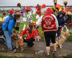 "Lutheran Church Charities ""comfort dog"" handlers Tom Bartnik, with Luther, and Jeanne Moore, with Aaron, visit the memorial along the fence of the Marysville-Pilchuck (Wash.) High School. (Ron Norris)"
