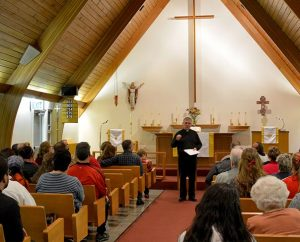 The Rev. Ron Norris, district disaster response coordinator for the LCMS Northwest District and an emergency-services chaplain, addresses worshipers after an Oct. 27 healing service at Messiah Lutheran Church, Marysville, Wash. (Richard Martin/Lutheran Church Charities)