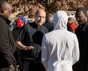 "From left, Vicar Chris Chandler, the Rev. Adam Filipek and the Rev. John Lewis talk to a protester in Ferguson, Mo., on Nov. 25. Synod leaders are making a plan to open a permanent ministry in Ferguson to ""rebuild hope and trust."" (LCMS/Erik M. Lunsford)"