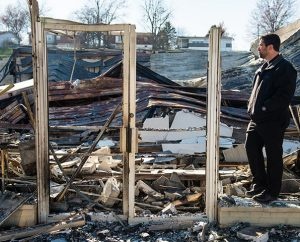 "The Rev. Ross Johnson, director of LCMS Disaster Response, surveys the burned-out shell of the Family Dollar store on Halls Ferry Road in St. Louis. Protesters in Ferguson are angrier than they were when Michael Brown was shot, but that's all the more reason for ""God's ambassadors"" to be there, Johnson said: ""People need to see that the church is present in times of turmoil."" (LCMS/Erik M. Lunsford)"