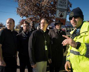 From left, the Rev. Adam Filipek, the Rev. Ross Johnson, the Rev. John Lewis, the Rev. Steven Schave and the Rev. Dr. Willie Stallworth talk to a state trooper in Ferguson, Mo., on Nov. 25. (LCMS/Erik M. Lunsford)