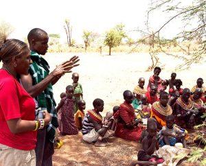 LCMS Missionary Shara Cunningham introduces herself to the Samburu people in Sirata, Kenya, Oct. 3 with the help of local evangelist Richard Lewaseiyan. (LCMS/Phil Jaseph)