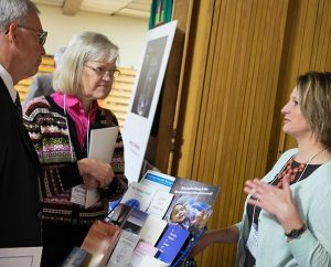 At the Lutherans For Life (LFL) exhibit for its 2015 national conference in Grand Rapids, Mich., LFL Data Analyst Jerilyn Richard, right, shares information about the organization with Rev. Lyndon and Linda Kohomen of Minneapolis. (Michael Schuermann)
