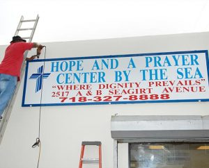 A worker hangs a sign for the Kenneth and Karen Ko Hope and a Prayer Center by the Sea in Far Rockaway, N.Y., on Oct. 29, the day the center was dedicated. The center, an outreach mission of the LCMS Atlantic District, is housed in three former storefronts. Before the center opened, the area was a regular spot for drug deals. (Doug Ross)