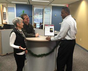 """From left, Concordia Plan Services (CPS) employees Maureen Schneider, Steve Gruenwald and Louis Johnson admire a framed copy of the St. Louis Business Journal article announcing CPS as a """"St. Louis Healthiest Employer"""" for 2014 — the third consecutive year that CPS has been chosen for the distinction."""