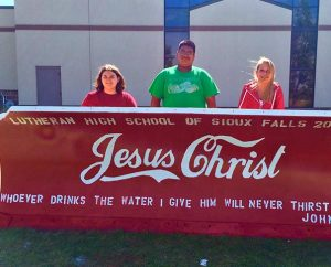 """Students from Lutheran High School of Sioux Falls (S.D.) pose with their Christian-themed entry in the city's """"Paint the Plows"""" contest. When a member of an atheist group complained about the artwork, Sioux Falls Mayor Mike Huether decided to leave the snowplow blades as is. (Lutheran High School of Sioux Falls)"""