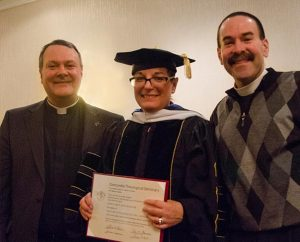 Dr. Maggie Karner stands with the Rev. Dr. Lawrence R. Rast Jr. (left), president of Concordia Theological Seminary, Fort Wayne, Ind., and her husband, the Rev. Kevin Karner, after receiving the Doctor of Humane Letters Honoris Causa Jan. 23. (LCMS/David Yow)