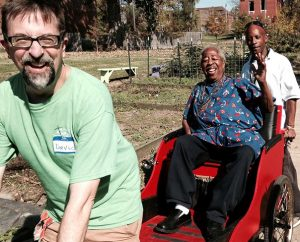 """The Rev. David McBurney, senior pastor of Abiding Savior Lutheran Church in south St. Louis County, gives Otis Woodard a rickshaw ride during an Oct. 25 servant event at Lutheran North St. Louis Outreach. Woodard """"personified the phrase 'servant leader,' """" McBurney told Reporter, and """"looked for opportunities to share the Gospel in word and deed."""" In the background is Abiding Savior sexton John Jones, who grew up in North St. Louis. (Joe Sell)"""