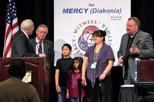 Retiring South Dakota District President Rev. Dr. Dale L. Sattgast, left, presents a gift to former LCMS missionary Amy Kashenov, second from right, to thank her for her service to Kazakhstan on behalf of the district. The work of Kashenov, who is now retired, was supported by the district for nearly 20 years. Also in the photo are, from left, the Rev. Dr. Ray Hartwig, LCMS secretary and Kashenov's father; Kashenov's children, Amanzhol and Kuralai; and Synod President Rev. Dr. Matthew C. Harrison. (South Dakota District)
