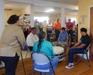 """The Rev. Will Main (at left, seated) joins other participants in a Native American """"honor ceremony"""" for Lutheran Church Extension Fund's Laborers For Christ this spring when work resumed on the new Haskell LIGHT Campus Ministry Center in Lawrence, Kan. (Haskell LIGHT Campus Ministry)"""