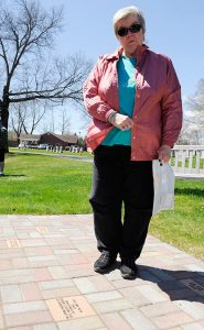 Dorothy Caruso of Schenectady, N.Y., stands before a paver in memory of her son, Vito Aristo Caruso, at Most Holy Redeemer Cemetery in Niskayuna, N.Y., where she had attended a memorial service for babies lost before and after birth. (Hans Pennink Special to Religion News Service)