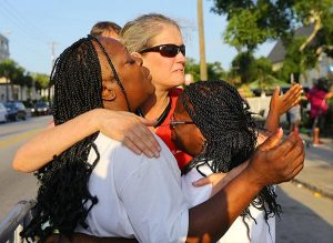From left, Crissa Jackson, Cynthia Coates and Cynthia Jackson embrace and pray as they wait for the doors to reopen to Emanuel A.M.E. Church in Charleston, S.C., on Sunday, June 21, 2015 — four days after the mass shooting there that claimed the lives of its pastor and eight others.  (Curtis Compton/Atlanta Journal-Constitution via AP)