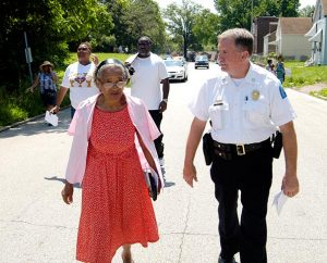St. Louis Metropolitan Police Department Sixth District Commander Capt. Kenneth Kegel walks with Ida Odom during Lutheran Housing Support's Peace and Praise Walk June 6. (James H. Heine)