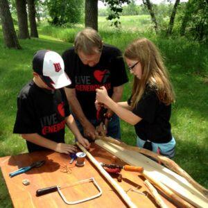 "A: Norman Barge, a longtime camp volunteer, teaches ""Prairie and Woods"" campers at Christ Serve Ranch, Henning, Minn., how to make walking sticks. (Judy Kretzschmar)"