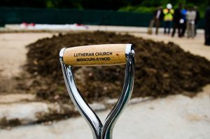 The Lutheran Church—Missouri Synod — noted on the handle of the shovel used by the Rev. Steven Schave at the recent groundbreaking — is one of four partners that will offer services at the new Community Empowerment Center of Ferguson, to open in summer 2016. (LCMS/Frank Kohn)