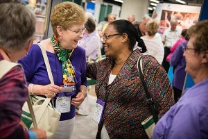 Lois Pohlmann, left, and Tadelech Loha Shumbio greet each other in the exhibit hall of the 36th Biennial Convention of the Lutheran Women's Missionary League in Des Moines, Iowa. (LCMS Communications/Erik M. Lunsford)
