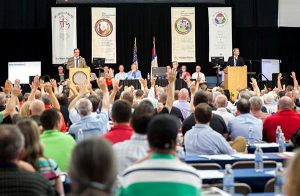 Delegates to the LCMS Michigan District convention respond to a question with a show of hands. At the podiums are, from left, district President Rev. Dr. David P.E. Maier and First Vice-President Rev. Mark Brandt. The convention was June 28-30 at Concordia University, Ann Arbor, Mich. (Elisa Schulz)