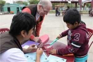 Team member in Peru teach dental health on a Community Health Education trip