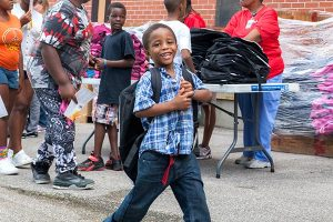 """A young guest at Concordia Publishing House's Aug. 6 """"Operation F.U.N."""" event tries on his new backpack. He was one of 850 area children who received the free backpacks filled with school supplies at CPH's 20th annual neighborhood-outreach party. (Amanda Lansche)"""