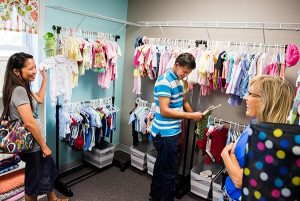 """From left, Sweet Rose and Arnie Suan chat with Barb Erickson in the boutique of donated baby clothes and supplies during an Aug. 15 tour of the newly-opened Iowa Life Care Clinic in Creston, Iowa. The clinic opened out of a former Planned Parenthood facility once known for its controversial """"telemedicine"""" abortions. (LCMS/Erik M. Lunsford)"""
