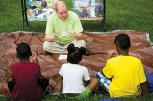 The Rev. Adam Filipek, pastor of Salem Lutheran Church in nearby Black Jack, Mo., shares a Bible story with children. (LCMS/Frank Kohn)