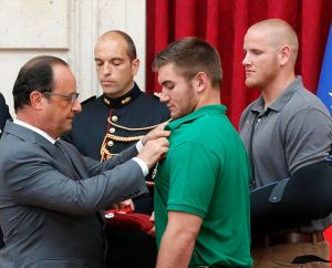 French President François Hollande, left, awards the Legion d'Honneur, Aug. 24 to Alek Skarlatos, a U.S. National Guardsman and Lutheran from Roseburg, Ore., while Airman 1st Class Spencer Stone looks on at the Elysee Palace in Paris. Hollande also pinned Legion d'Honneur medals on Stone and Anthony Sadler. The three men, lifelong friends, were honored for subduing a gunman Aug. 21 as he moved through a train with an assault rife strapped to his chest. (AP Photo/Michel Euler, Pool)