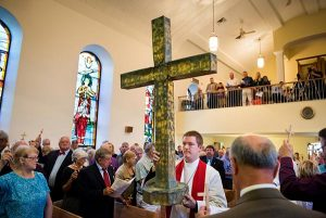 """The Rev. Jacob Mueller of Holy Cross Lutheran Church in Emma, Mo., carries the former steeple cross of St. John's Lutheran Church as crucifer before worship, Aug. 9, during a """"Day of Thanksgiving and Rededication"""" at the church in New Minden, Ill. Nearly two years ago, a tornado damaged the church and surrounding homes, and toppled the cross, which was later placed next to the rededicated altar. (LCMS/Erik M. Lunsford)"""