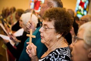 """Parishioners lift high crosses constructed from the wood of the former steeple of St. John's Lutheran Church, which was damaged nearly two years ago from a tornado, during the congregation's """"Day of Thanksgiving and Rededication."""" (LCMS/Erik M. Lunsford)"""