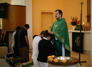 The Rev. Dr. Gottfried Martens, pastor of Trinity Lutheran Church in Berlin-Steglitz, prays with people from Iran during a Baptism service at Trinity Aug. 30. Hundreds of asylum-seekers reportedly have converted to Christianity at Trinity, a church that is part of the Selbständige Evangelisch-Lutherische Kirche (SELK), an LCMS partner church. (AP Photo/Markus Schreiber)