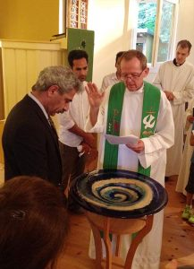 Rev. Hugo Gevers prays for Eizadi Shahriyar during a Farsi and German Baptismal Rite, July 27, 2014, at St. Trinitatisgemeinde in Leipzig, Germany. Shahriyar continues to be an active member of the congregation. Gevers is a missionary to migrants and the underserved in Volkmarsdorf in Leipzig for the Selbständige Evangelisch-Lutherische Kirche (SELK), an LCMS partner church. (Coiurtesy of St. Trinitatisgemeinde)