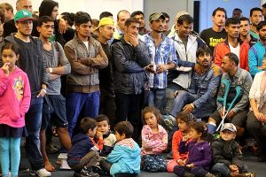 Refugees with their children watch Berlin's Governing Mayor Michael Mueller (unseen) deliver remarks during his visit to Karlshorst emergency shelter in Berlin, Germany, Sept. 14.  (AP/Wolfgang Kumm)