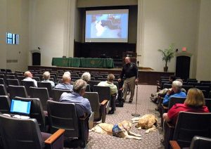 """Tim Hetzner, president of Lutheran Church Charities, leads a presentation on using """"K-9 Comfort Dogs"""" in disaster response. Hetzner described the golden retrievers as """"lovers"""" by nature who are """"great listeners and nonjudgmental."""" The photo on the screen behind him shows a young man lying on a floor with comfort dog """"Howie."""" The young man — who was grieving his girlfriend, who died in a car accident — stayed with the dog for 45 minutes, Hetzner said. (LCMS/Paula Schlueter Ross)"""