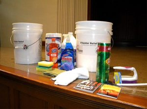 """Among the contents of a typical """"flood bucket"""" — on display at the conference — are bleach and other cleaners, paper towels, a scrub brush, sponges, disposable gloves and towels. Flood buckets — used for cleanup — should always have a lid to prevent items from spilling out. (LCMS/Paula Schlueter Ross)"""