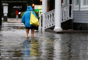A woman walks down a flooded sidewalk toward an open convenience store in Charleston, S.C., Oct. 4. The Rev. Michael Meyer, disaster-response manager for the LCMS Office of National Mission, has deployed to assist the LCMS Southeastern District in essential damage assessments as flooding continues in South Carolina. (AP Photo/Chuck Burton)
