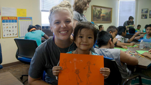Young Adults Ministry Servant Event participant interacts plays with a refugee child at a Christian Friends of New Americans event.