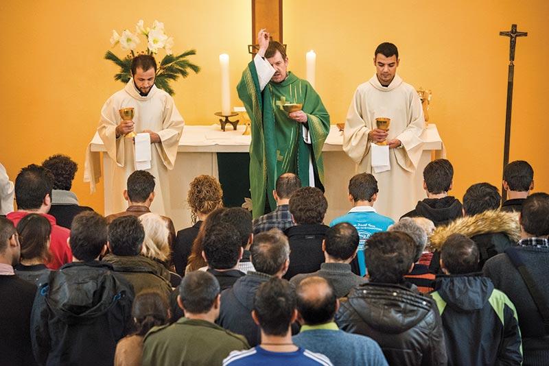 Refugees gather for communion and blessings as the Rev. Dr. Gottfried Martens leads worship on Sunday, Nov. 15, at the Dreieinigkeits-Gemeinde, a Selbstandige Evangelisch-Lutherische Kirche (SELK) church in Berlin-Steglitz, Germany. (LCMS/Erik M. Lunsford)