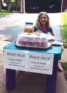 """Abby Sommer, whose father is a student at Concordia Seminary, St. Louis, sells cupcakes outside her home in May. She raised $36 for the LCMS Joint Seminary Fund, and mailed it to the fund along with a note that said, in part, """"We hope you and others are mightily blessed by this."""" (Courtesy of Sommer family)"""