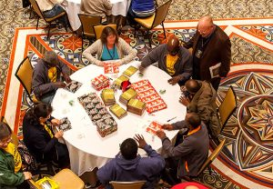In a two-hour Nov. 20 servant event, participants at the 2015 Lutheran Church Extension Fund Fall Leadership Conference in Atlanta, assemble items including Bibles and messages of hope to fill 500 backpacks for homeless people served by the city's Stepping Stone Mission, an LCMS Recognized Service Organization. (Lutheran Church Extension Fund)