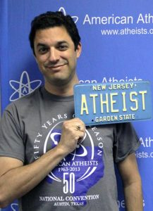 """David Silverman poses with a retired """"ATHEIST"""" New Jersey plate. (Courtesy of Dave Muscato/American Atheists)"""
