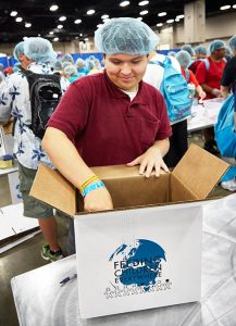 """A participant at the 2013 LCMS Youth Gathering in San Antonio places packaged meals into a box to be sent out to people who need food. That effort provided more than 322,000 meals. Supporters of LCMS Youth Ministry's """"WeRaise"""" crowdfunding campaign pledged a total of $25,000 that, when combined with registration fees and a grant from LCMS mercy ministries, allows for 500,000 meals to be packed at the 2016 LCMS Youth Gathering. (Anna Sparks/Gathering Media)"""