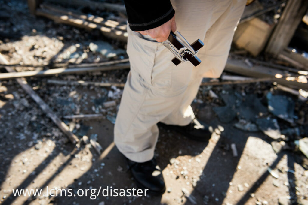 The Rev. Steven Schave, director of LCMS Urban & Inner-City Ministry, carries a cross as he surveys the remnants of the Family Dollar Store on Halls Ferry Road on Tuesday, Nov. 25, 2014, in St. Louis. The building caught fire the previous night following a grand jury decision not to indict Ferguson Police Officer Darren Wilson in the shooting death of Michael Brown. LCMS Communications/Erik M. Lunsford