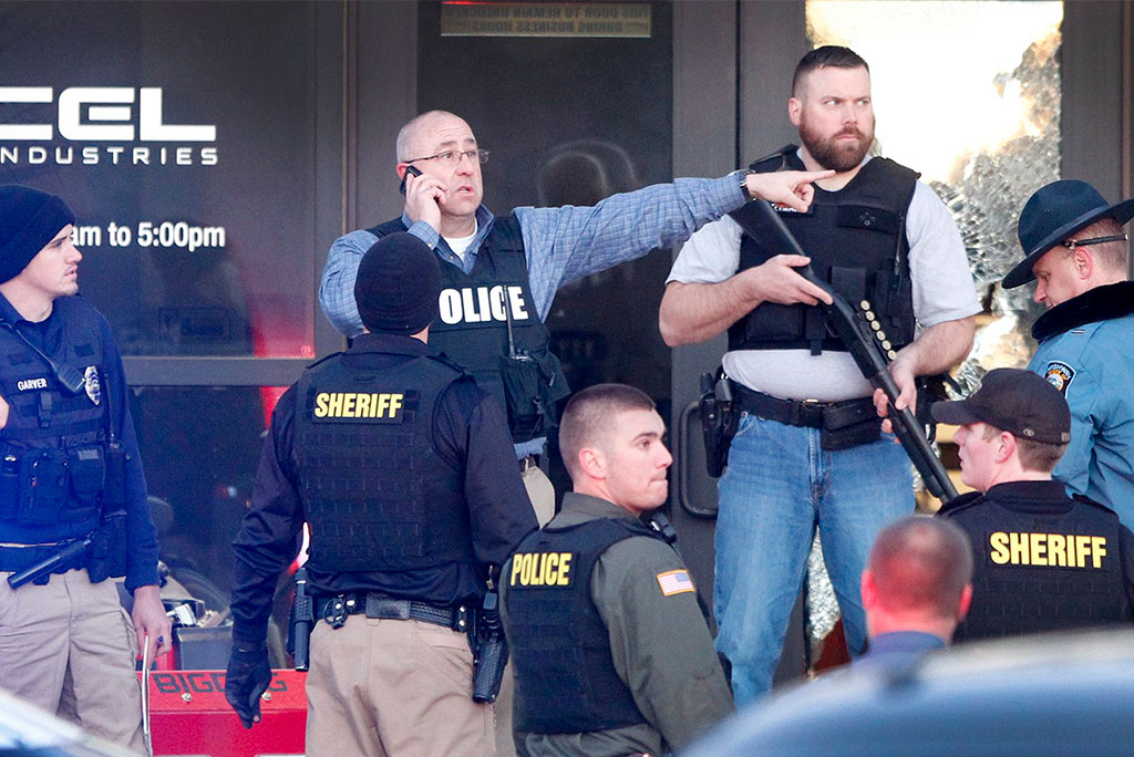 Police guard the front door of Excel Industries in Hesston, Kan., Feb. 25, where a gunman's rampage ended after he killed three people and left 14 others injured. (Fernando Salazar/The Wichita Eagle via AP)